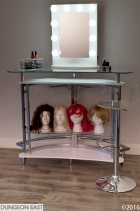 Vanity mirror, make-up and wigs.